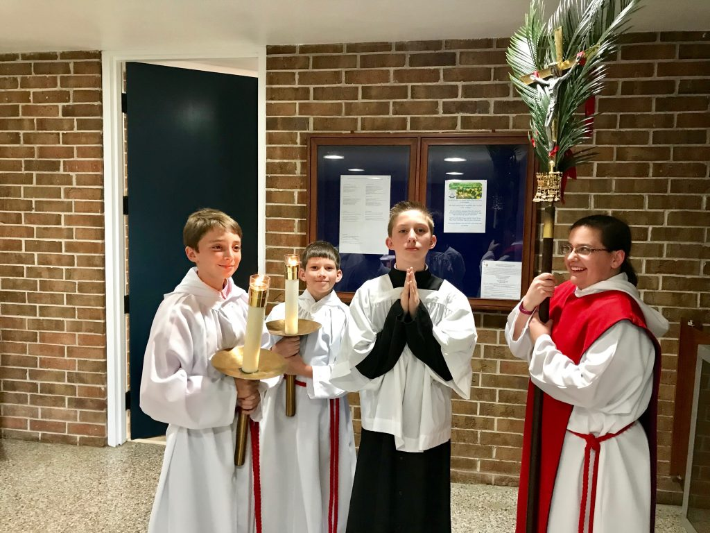 Altar servers with candles and crucifix