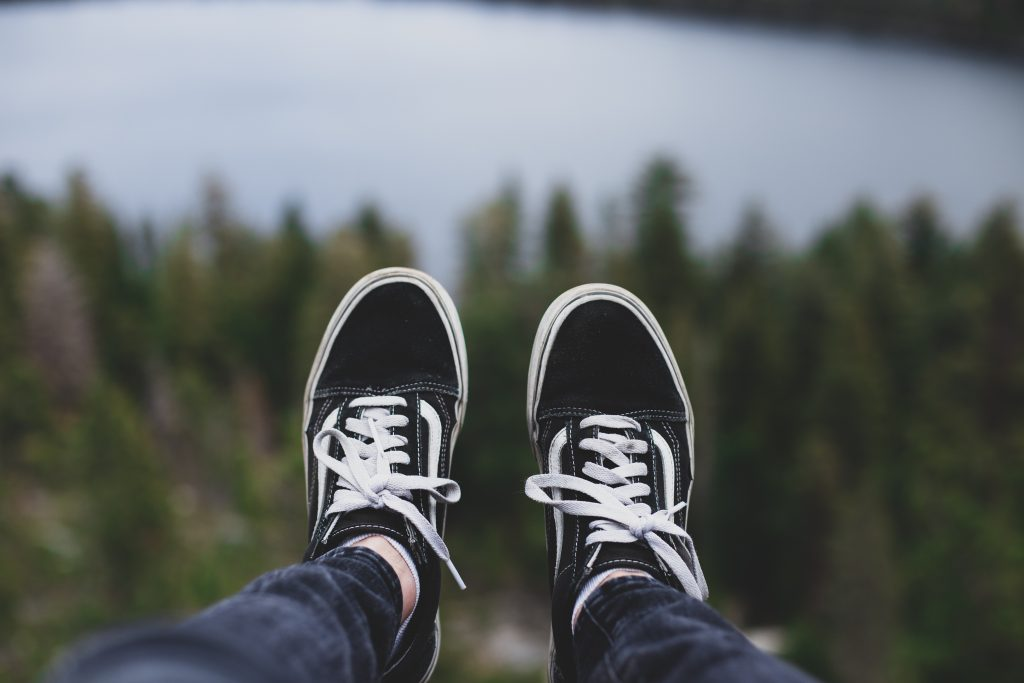Person feet with lake and forest in the background